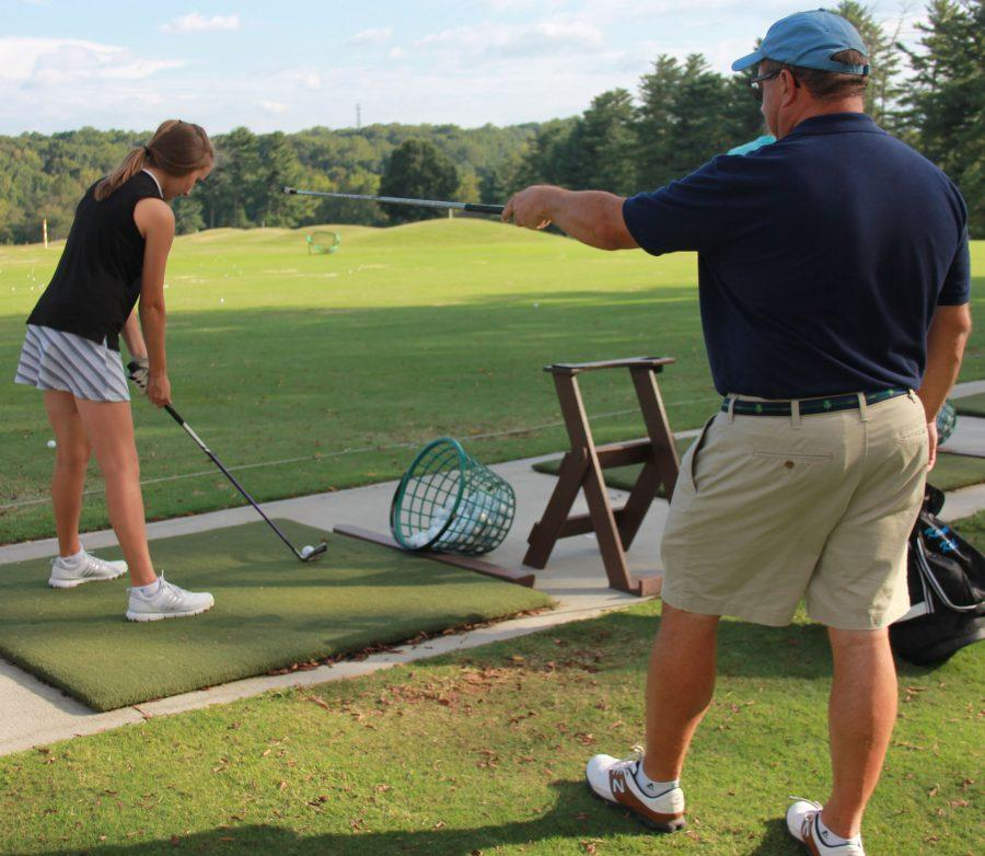 Coach Jay Allred helps freshman Kathryn Krull on the driving range. Allred was voted Coach of the Year for the Central Piedmont Conference.