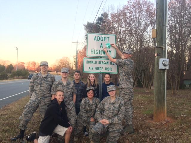 Members+of+Reagan%27s+AFJROTC+pose+in+front+of+the+Adopt+a+Highway+sign.+One+cadet+places++the+ten+year+award+on+the+sign.