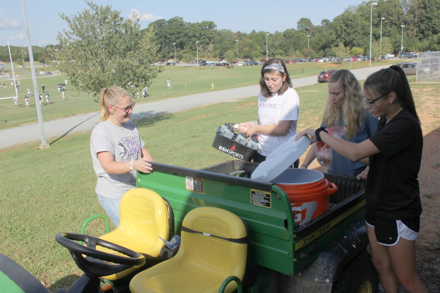 (From left to right) Senior Alyssa Taylor, juniors Hannah Bryan and Sam Dembosky, and sophomore Michelle Salus load the Gator with materials for football practice. Salus is the only returning trainer from last year.