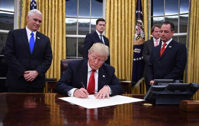US President Donald Trump signs an executive order as Vice President Mike Pence and Chief of Staff Reince Priebus look on at the White House in Washington, DC on January 20, 2017. / AFP PHOTO / JIM WATSONJIM WATSON/AFP/Getty Images