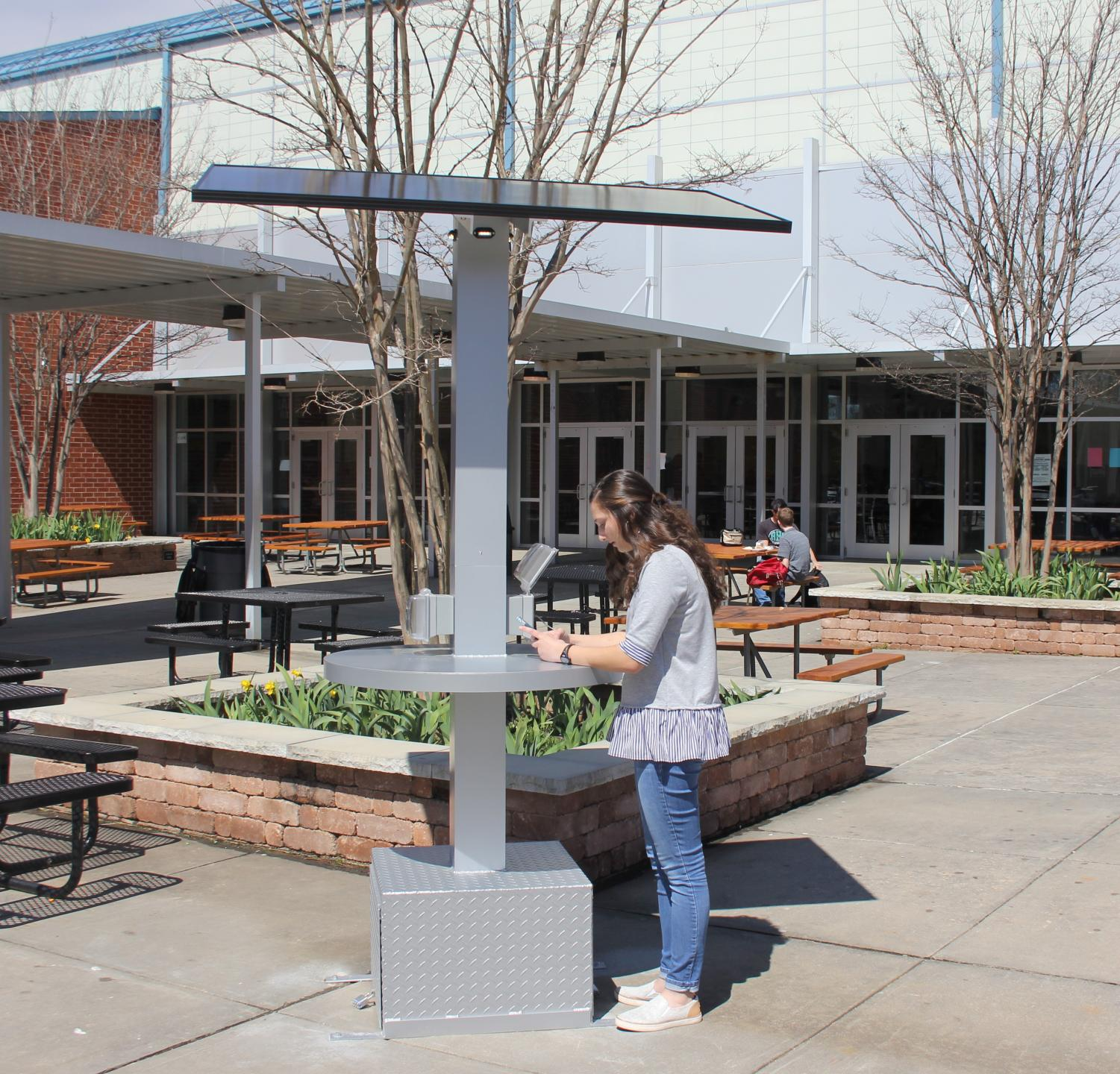 Senior Haylie Paulin, charges her phone on the new solar charing panels. Science teacher Ed Thutt won the solor panel by applying for a grant.