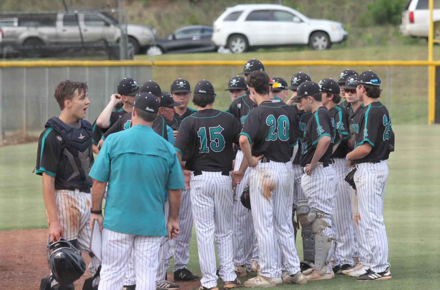 The team huddles in between innings during a state playoff game versus Ragsdale. The Raiders won 6-0 against the Tigers on May 9.