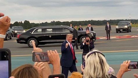 Trump arrives at Smith Reynolds Airport. He walks down the runway and waves at the crowd.
