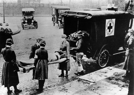 A Spanish flu victim is being carried by American Red Cross volunteers. The disease spread was prevalent, and it's estimated that 20 to 100 million people were killed by it worldwide.