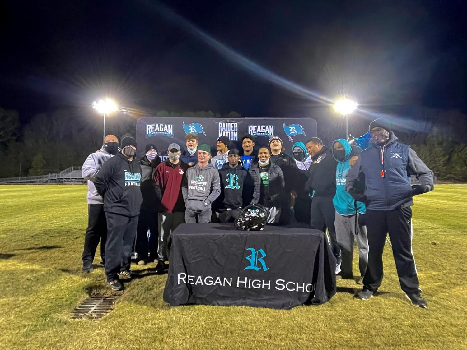 Reagan seniors on the football team join together with their head coaches after signing. The senior class of 2021 is the first group to sign for colleges in all levels of collegiate athletics.