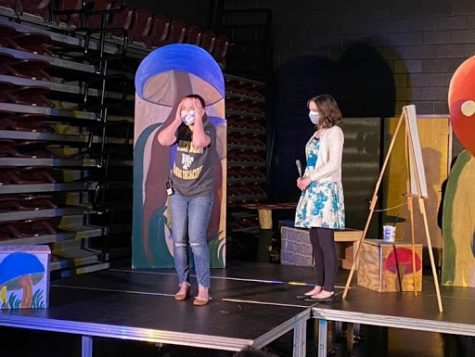 "Actresses Elizabeth Gambill (12) and Alyssa Eaton (12) practice their lines at a dress rehearsal of ""Alice in Wonderland."" The play will be performed in the bus lot of Reagan's campus."